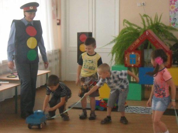 Дети играют с машинками в группе, рядом стоит педагог в форме полицейского