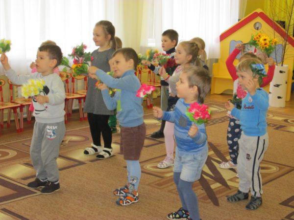 Дети с искусственными букетиками наклоняются в стороны
