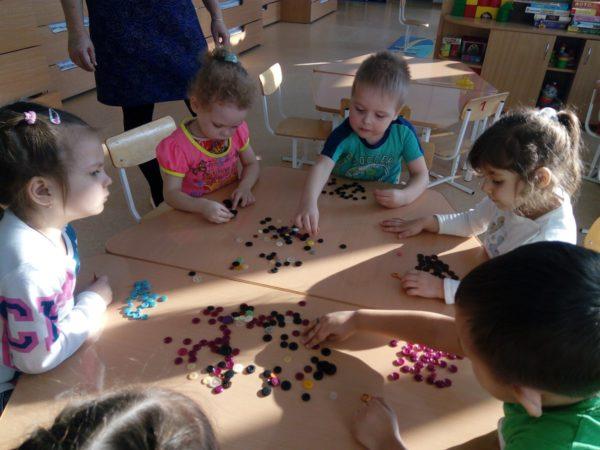 Дети, сидя за столом, раскладывают пуговицы