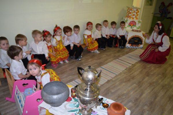 Дети сидят на стульях по периметру комнаты, воспитательница в народном костюме, некоторые дети тоже