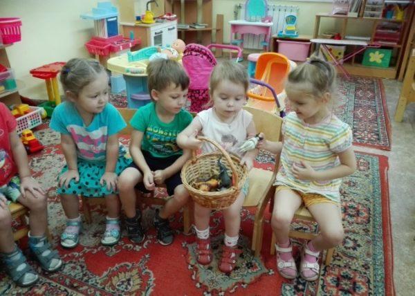 Дети сидят на стульях, у девочки в руках корзинка