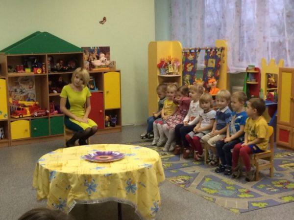 Дети сидят на стульях, воспитательница смотрит в сторону зрителей, на переднем плане стол, застеленный скатертью