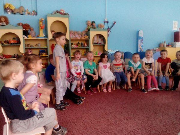 Дети сидят полукругом, мальчик стоит и что-то говорит