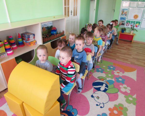 Дети сидят в парах друг за другом, изображая автобус