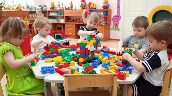 Дети сидят за столом и работают с конструктором