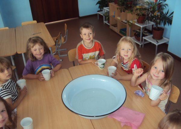 Дети сидят за столом, по центру которого миска с водой