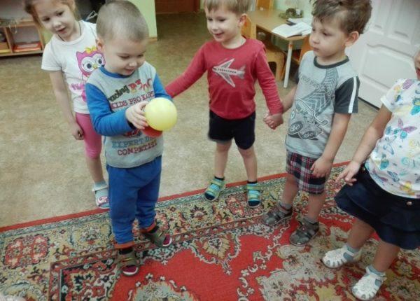 Дети стоят кругом, взявшись за руки, мальчик держит жёлтый мячик