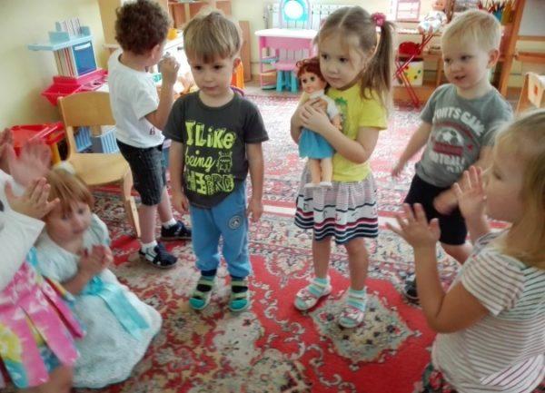 Дети стоят полукругом, девочка прижимает к себе куклу