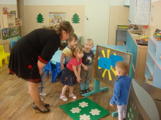 Дети стоят у доски с солнышком, закрытым тучами, воспитательница комментирует