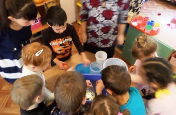 Дети стоят вокруг стола с пластиковыми стаканчиками с семенами