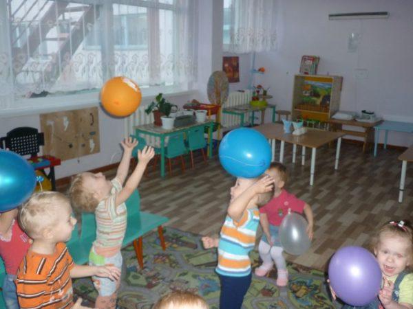 Дети в группе играют воздушными шарами