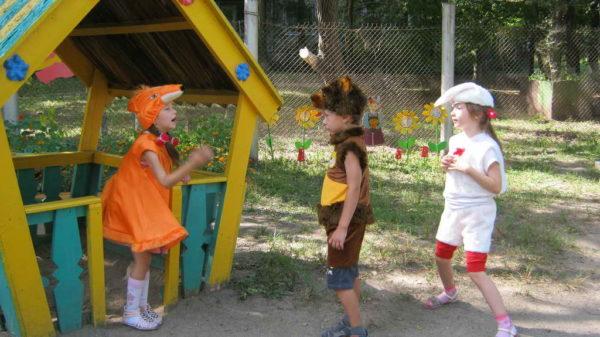 Дети в костюмах лисички, медведя и зайца во дворе рядом с домиком-бесед