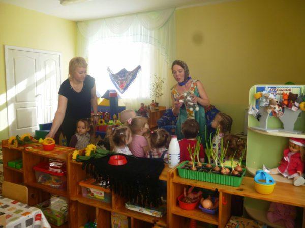 Дети в уголке природы смотрят на воспитательницу в платочке, которая держит мягкую игрушку