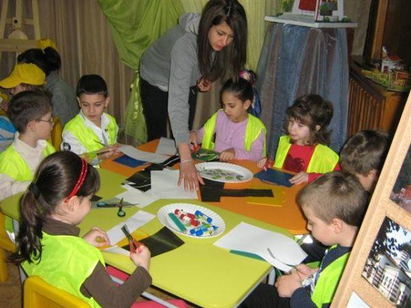 Дети в жёлтых жилетах вырезают из бумаги