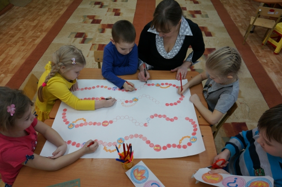 Дети вместе с воспитателем рисуют поле для настольной игры