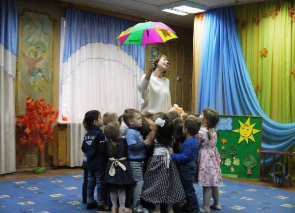 Дети вокруг воспитательницы с зонтом