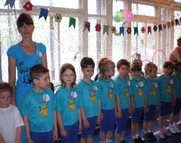 Дети, воспитательница в синих футболках стоят на занятии физкультурой