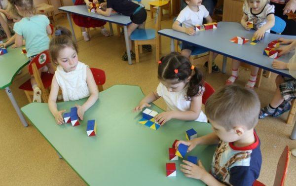 Дети за столами накладывают кубики на картинки