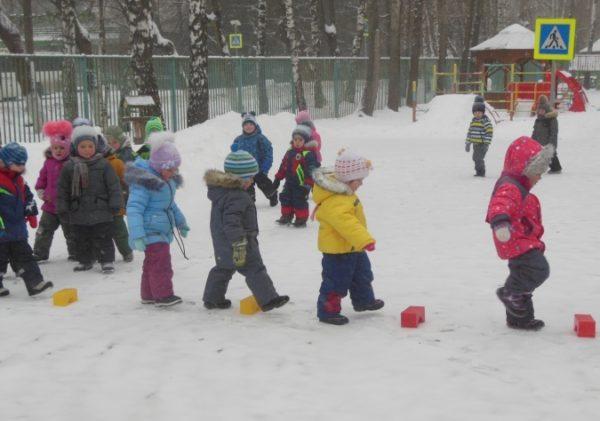 Дети зимой идут вдоль выложенной кубиками дорожки