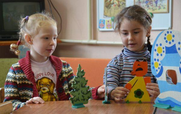 Две девочки, сидя за столом, разыгрывают сказку