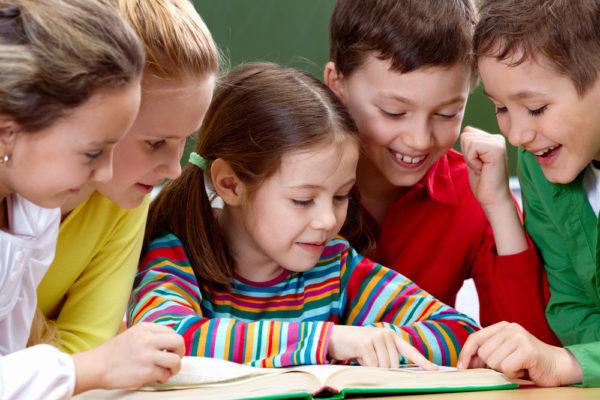 Девочка читает книгу двум мальчикам и двум взрослым