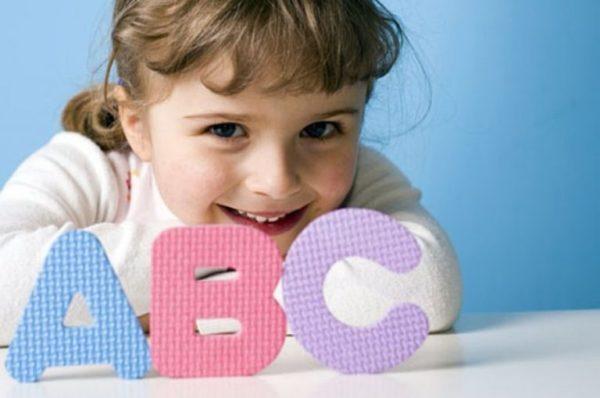 Перед улыбающейся девочкой на столе стоят три буквы