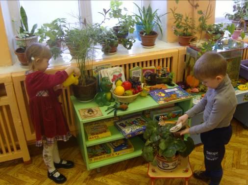 Девочка из жёлтой лейки поливает цветок, а мальчик протирает листья на другом
