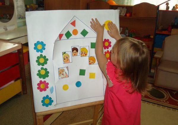 Девочка крепит на лист с изображением домика и людей жёлтый кружочек