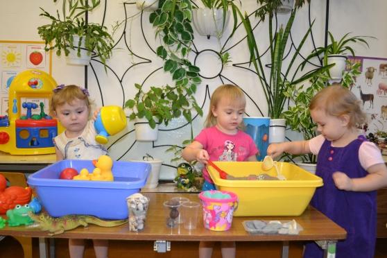Три девочки играют с песком и водой в помещении группы