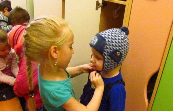 Девочка помогает маленькому мальчику надеть шапку