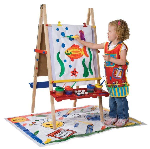 Девочка рисует красками на мольберте