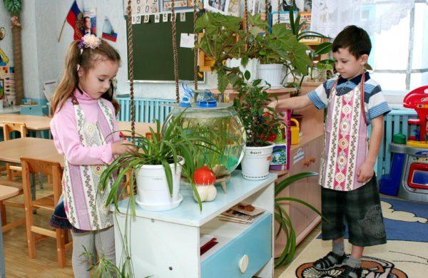 Девочка рыхлит землю в цветочном горшке, а мальчик поливает стоящий рядом цветок
