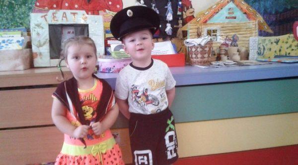 Девочка с коричневым платочком на плечах и мальчик в коричневых шортах и фуражке