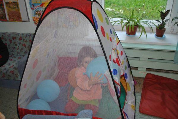 Девочка сидит в домике для уединения