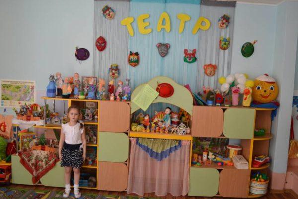 Девочка стоит на фоне уголка под названием Театр