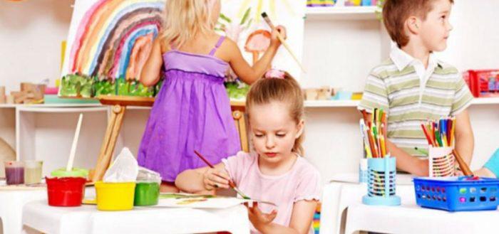 Девочка, стоящая спиной, рисует солнце на мольберте, девочка справа рисует красками, мальчик слева смотрит в сторону