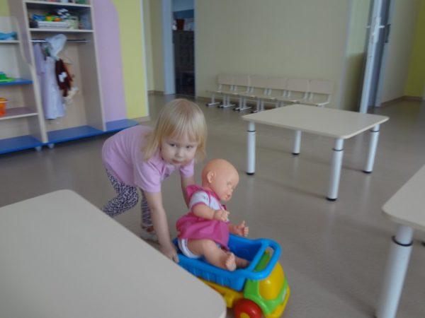 Девочка везёт куклу на игрушечной машине