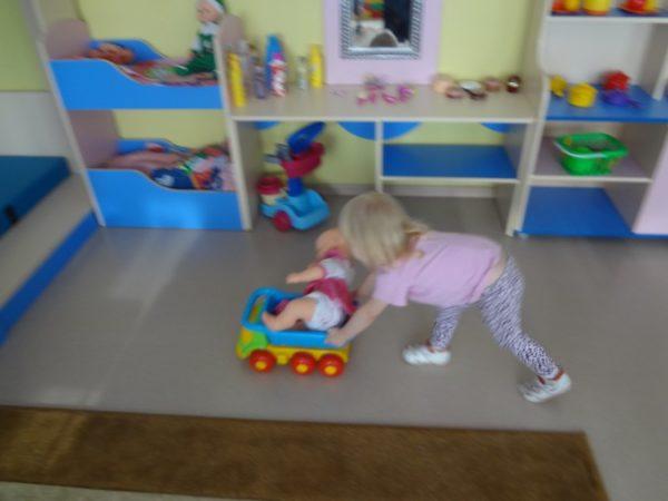 Девочка везёт машину с куклой