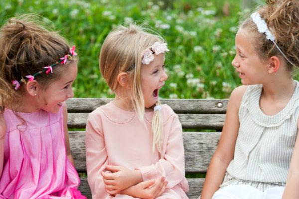 Три девочки общаются, сидя на лавочке