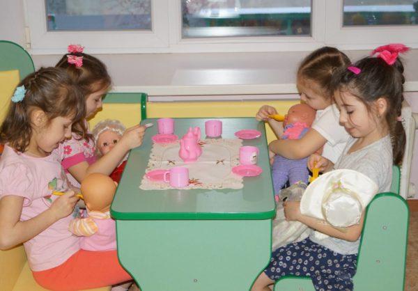 Девочки кормят кукол-младенцев в кафе