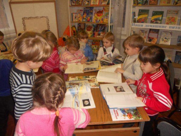 Дошкольники листают книги, разложенные на столе