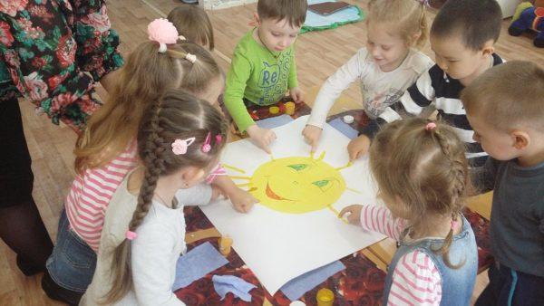 Дошкольники вместе рисуют лучики изображённому на ватмане солнышку