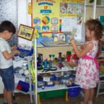 Мальчик и девочка рассматривают материалы в исследовательском уголке