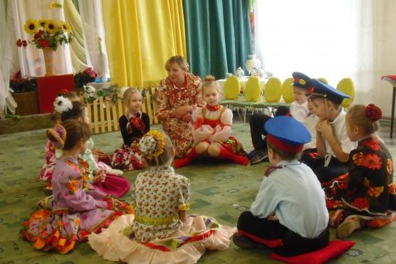 Дети и педагог в костюмах участвуют в досуге «Казачьи посиделки»