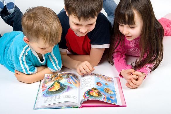 Два мальчика и девочка, лёжа на животе, читают книгу с картинками