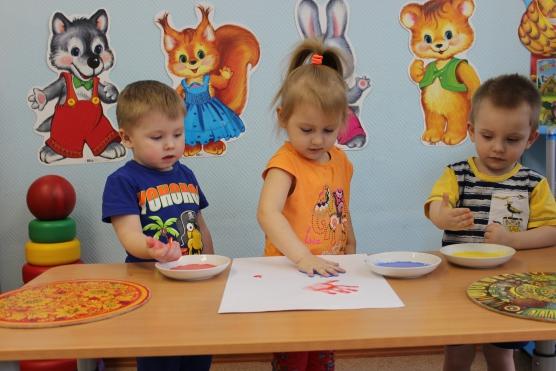 Два мальчика и девочка рисуют ладошками, на заднем фоне изображения лисички, волка, зайца, медведя