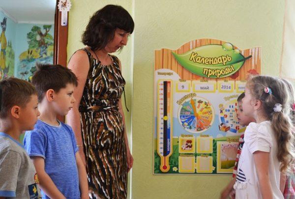Два мальчика и девочка с воспитательницей обсуждают календарь природы