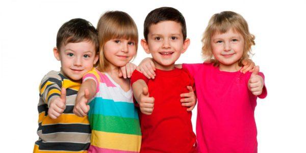 Две девочки и два мальчика, обнявшись, показывают большие пальцы вверх