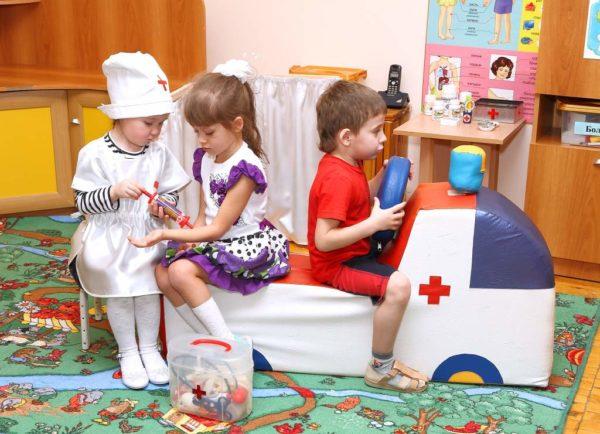 Две девочки и мальчик играют в скорую помощь с водителем на машине-батуте, доктором и пациентом