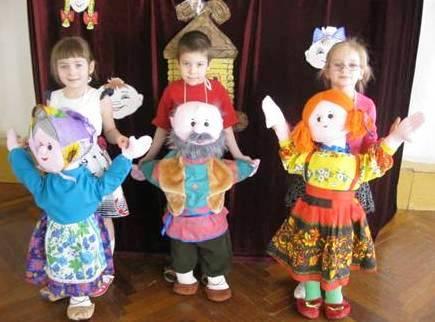 Две девочки и мальчик с куклами с куклами на фартуке